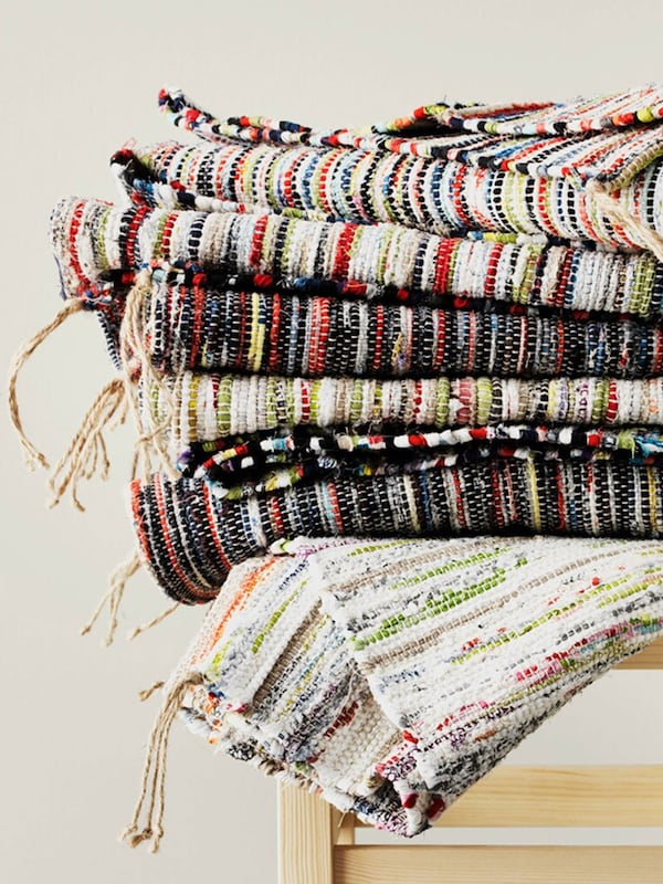 A picture of colorful IKEA woven rugs piled on top of each other on a stool which have been made from leftover fabrics.