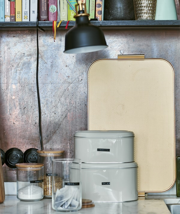 A picture of storage jars, tins and a tray against a copper wall.