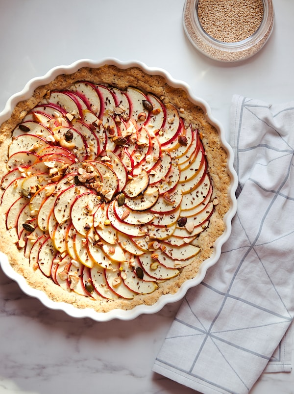 A pie covered with thin apple slices, seeds and nuts in a white VARDAGEN pie dish standing on a marble kitchen worktop.