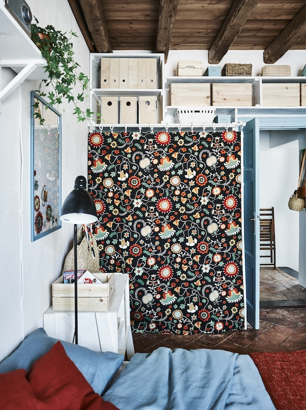 A piece of patterned fabric covering an open wardrobe.
