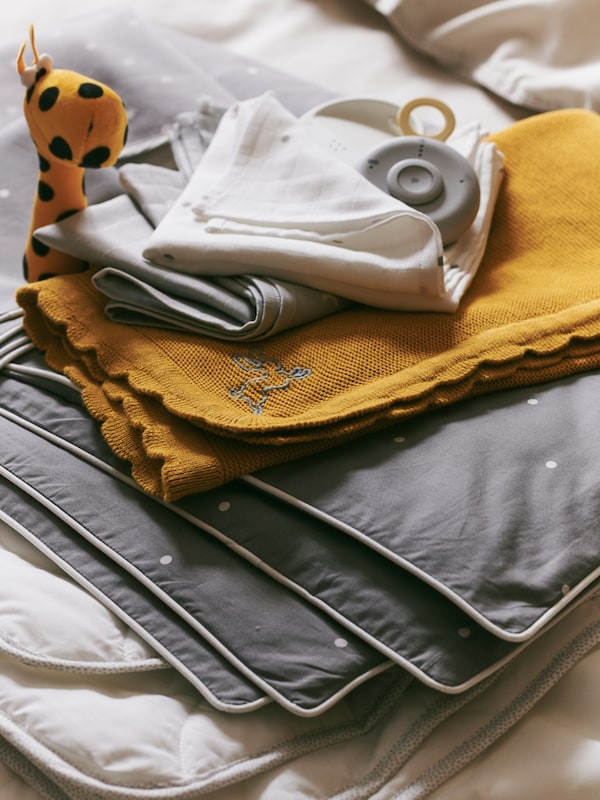 A pile of baby textiles including a dark yellow SOLGUL blanket and a LENAST cot quilt, with an UNDVIKA baby monitor on top.
