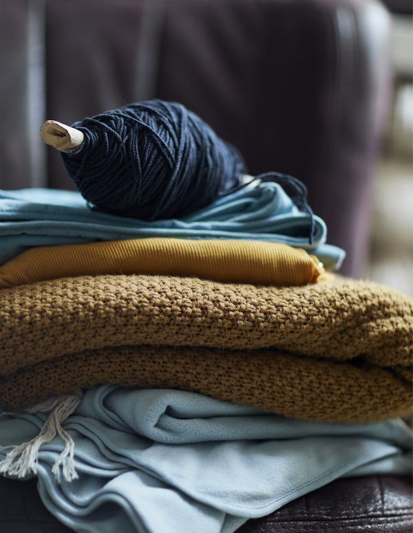 A pile of blue and yellow blankets and fabrics topped with a spool of wool.