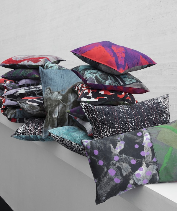 A pile of colourful and patterned cushions from the IKEA ANNANSTANS collection on a white shelf.
