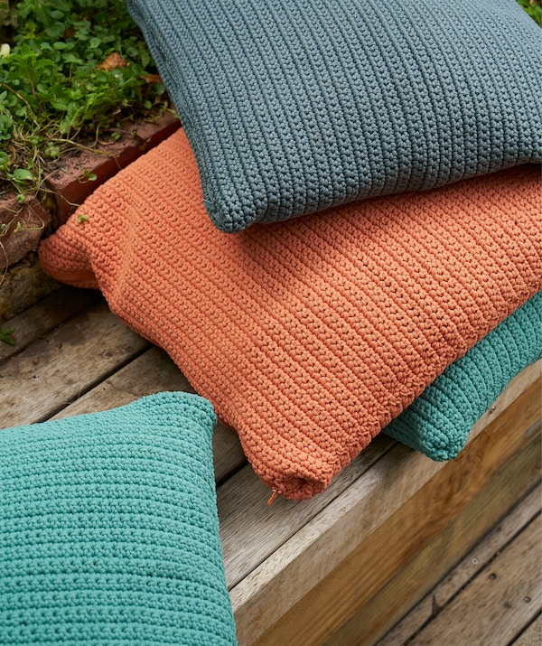 A pile of cushions in orange, blue and turquoise on wooden decking.