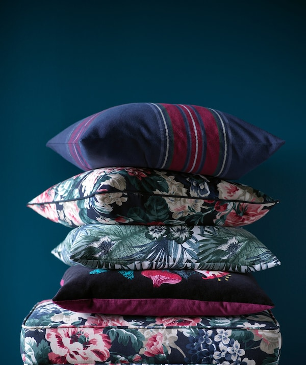 A pile of floral patterned cushions on a footstool.