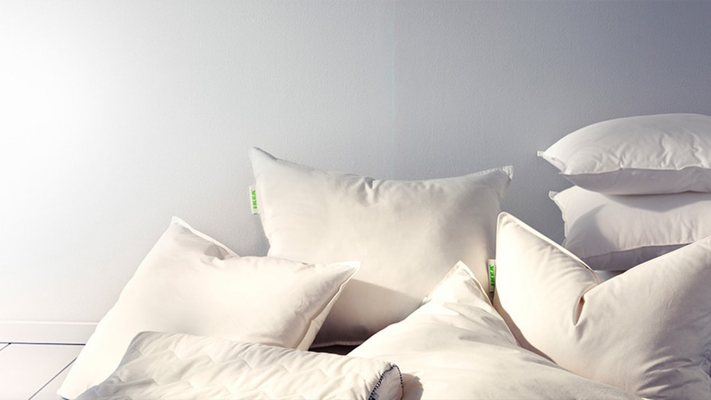 A pile of IKEA pillows on the floor against a white wall.