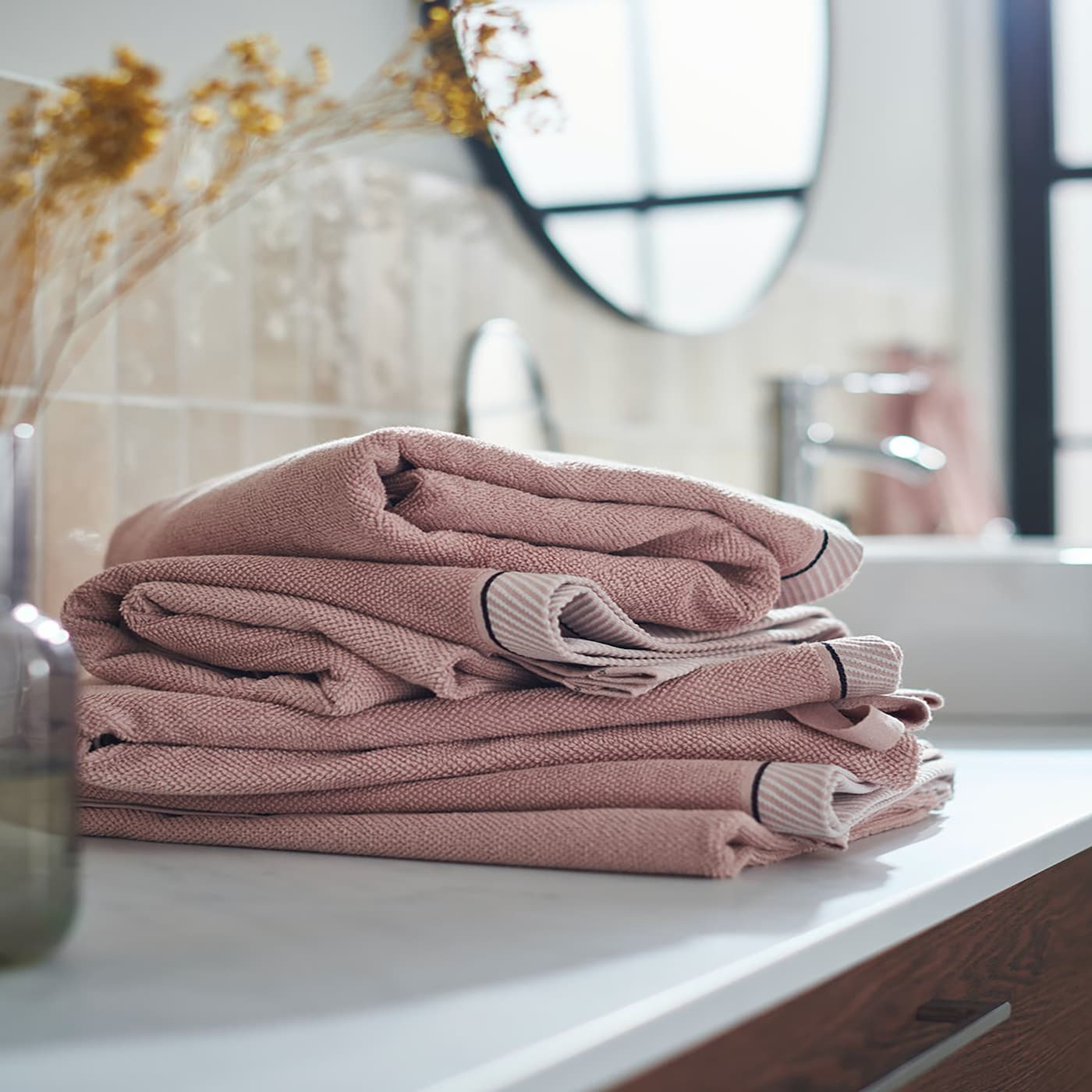 A pile of VIKFJÄRD hand towels in light pink stacked on a bathroom countertop.