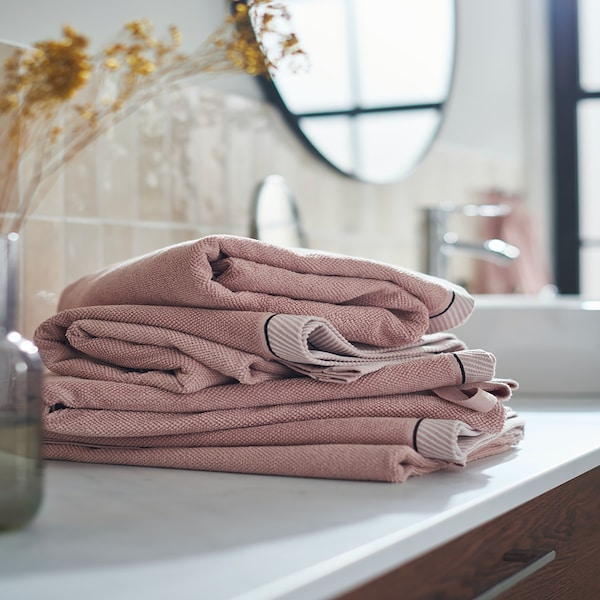 A pile of VIKFJÄRD hand towels in light pink stacked on a bathroom countertop
