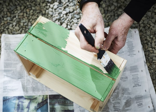 A pine box being painted with green paint.