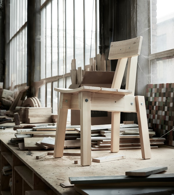 A pine chair standing on a work bench.