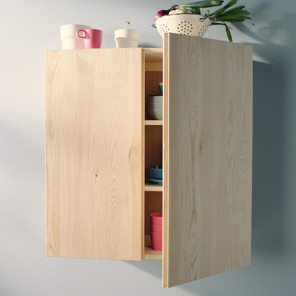 A pine, IVAR cabinet mounted on a wall with one door partially open, with objects inside and on top.