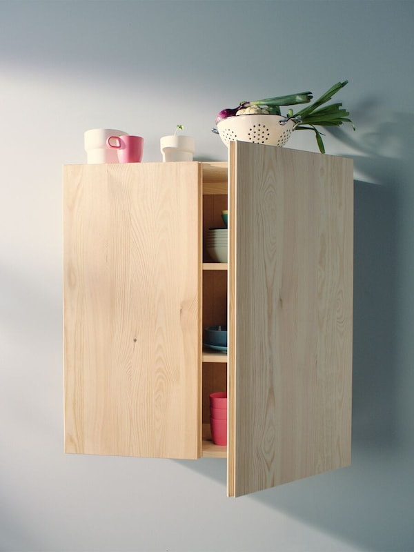 A pine, IVAR cabinet mounted on a wall with one door partially open, objects inside and on top.