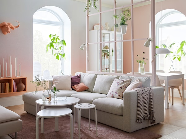 A pink and white living room with beige sofa with chaise longues and the hint of a dining area in the background.