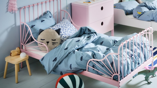 A pink kids bed with blue bedding with cars on it, and a pink chest of drawers next to the bed.
