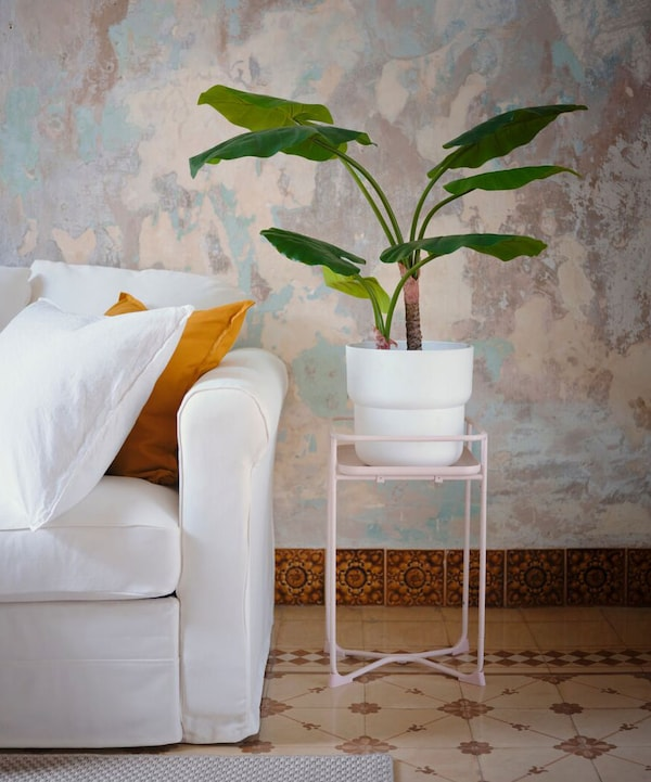 A pink KYRDDPEPPAR plant stand with potted plant atop next to the arm of a white, GRONLID sofa.