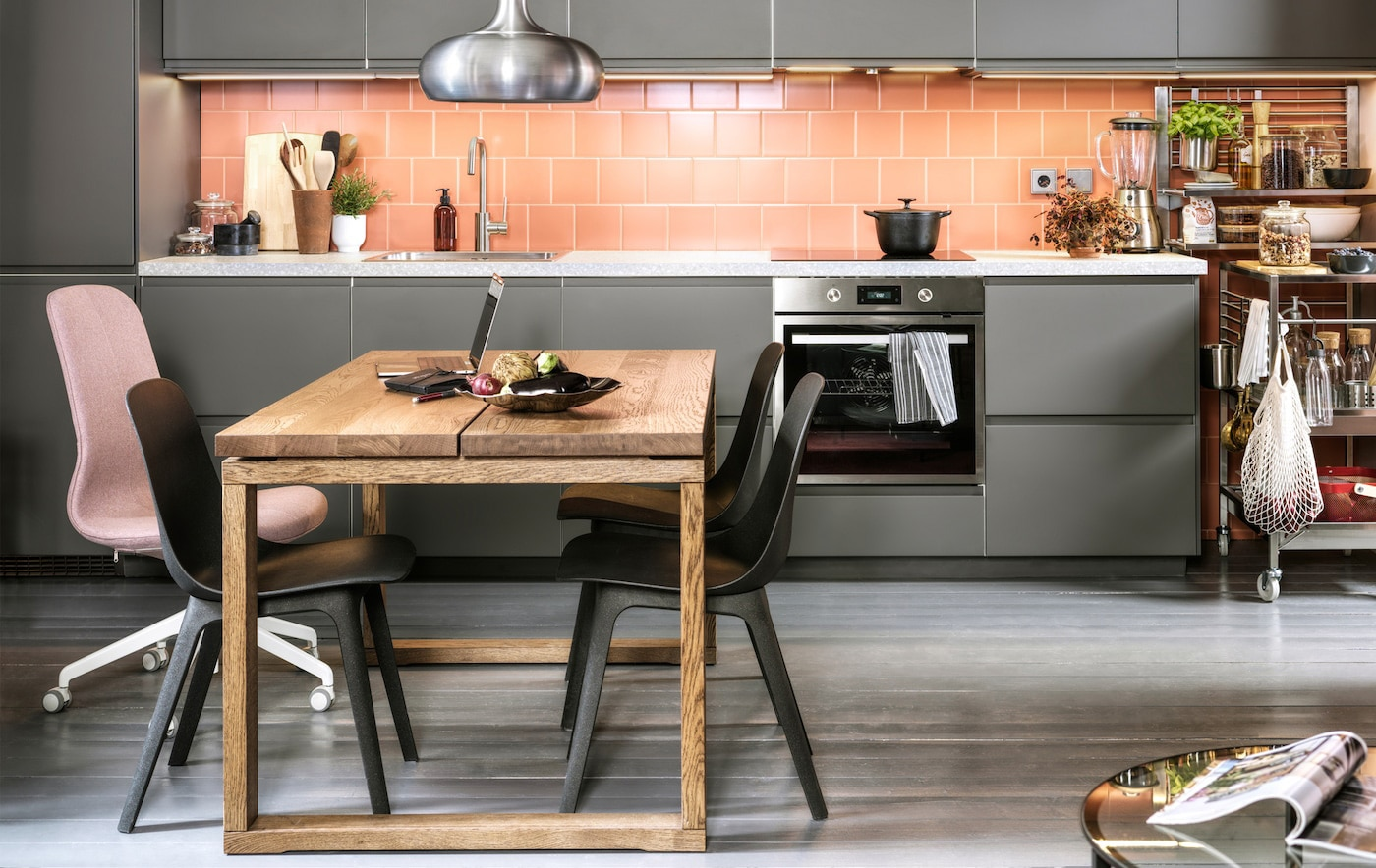 A pink-tiled kitchen with dark grey kitchen fronts, anthracite chairs, a dining table in oak veneer and a VÄXJÖ pendant lamp.