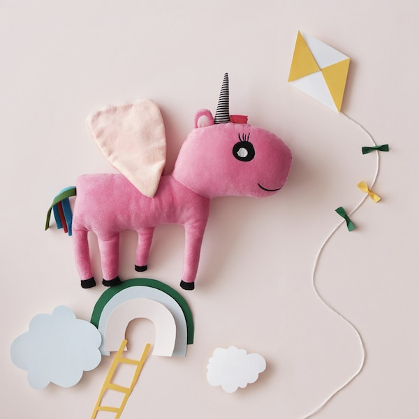 A pink unicorn soft toy in a paper cut-out sky scene.