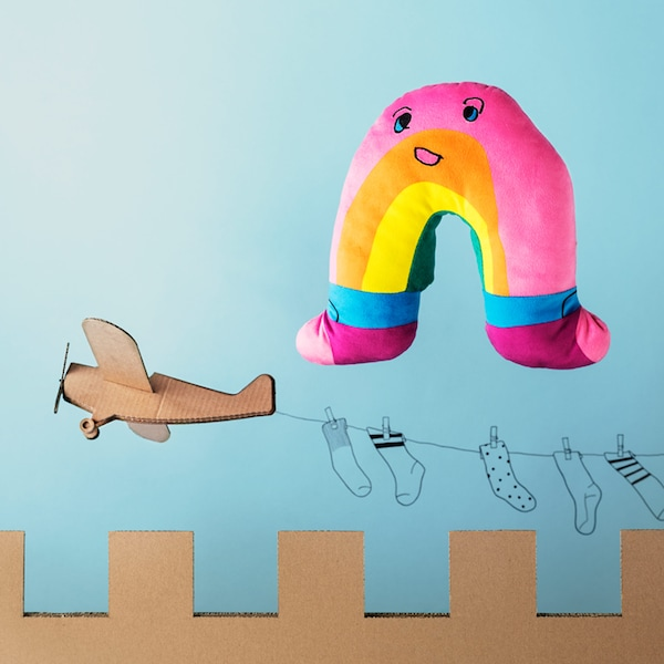 A pink, yellow and orange IKEA SAGOSKATT soft toy – a rainbow with socks floating over a cardboard castle.