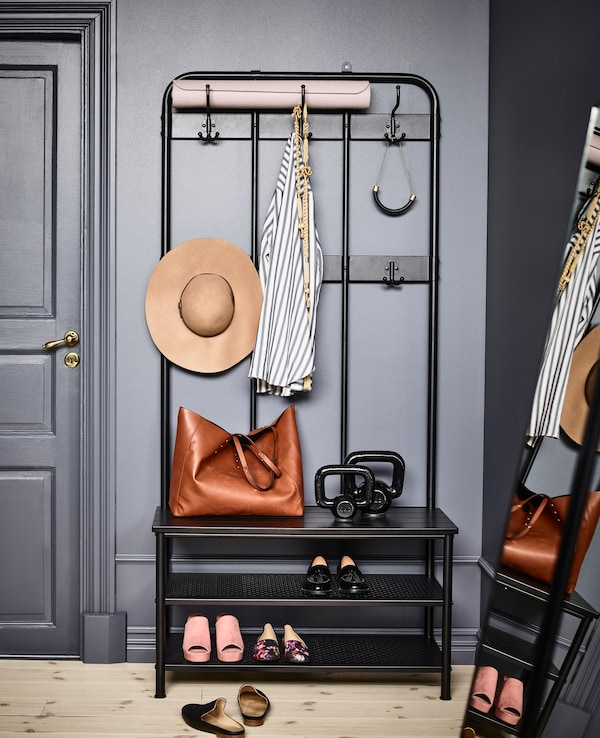 A PINNIG coat rack in black powder-coated steel and zinc stores clothes, shoes, and accessories in a grey bedroom.