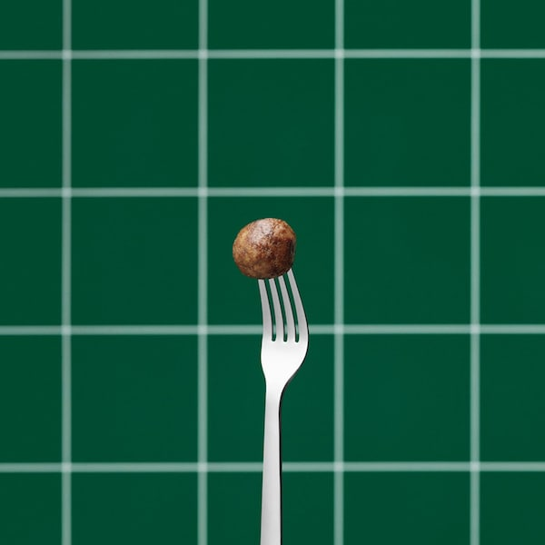 A plant ball on a fork with a green checkered background.