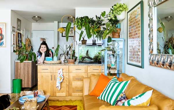A plant-filled, open-plan living space with a kitchen island, fish tank, sofa, cushions and coffee table, and wall decor.