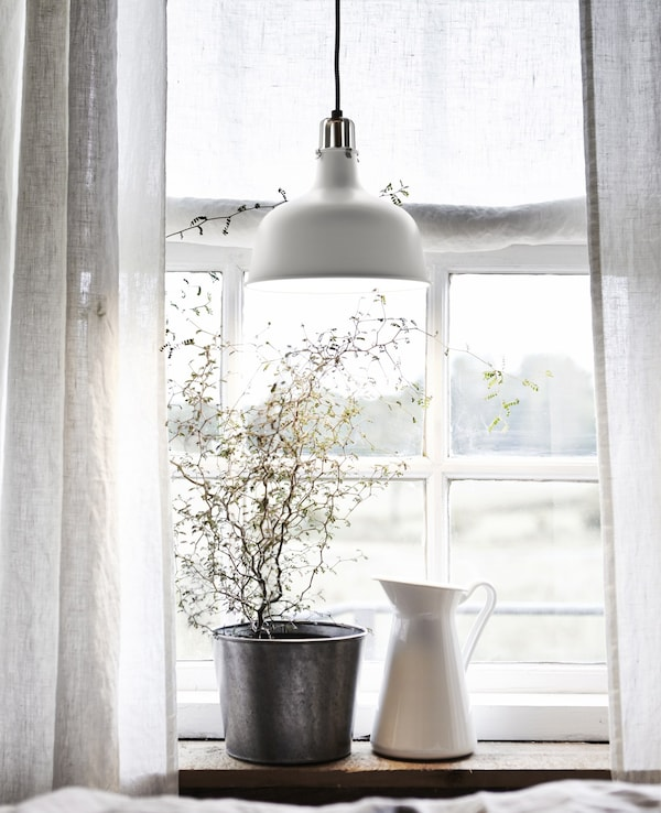 A plant in a dark pot and a white jug on a windowsill with white curtains and a white metal pendant lamp.