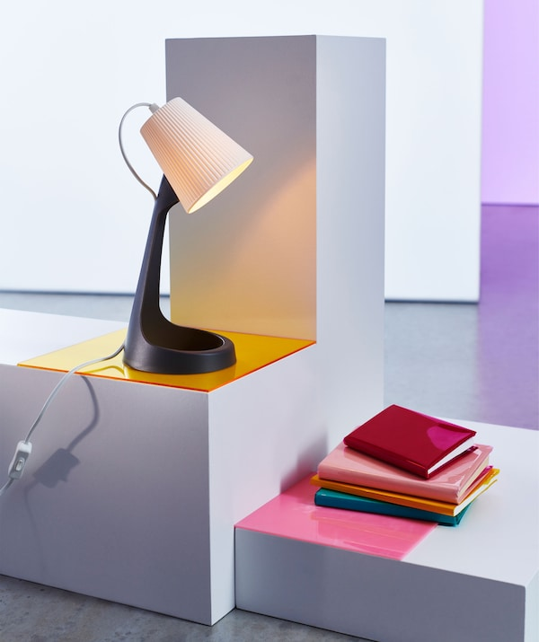 A plastic table lamp on a stand above a pile of books.