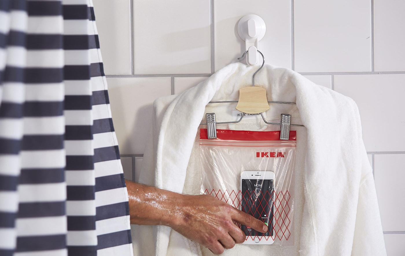 A plastic zip bag, pegged to a coat hanger, draped with a bath robe and used as a mobile phone holder.