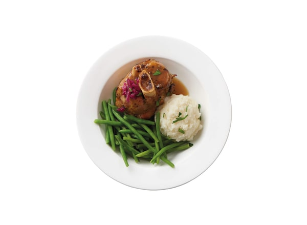 A plate of a braised pork shank with potatoes and green beans against a white background.