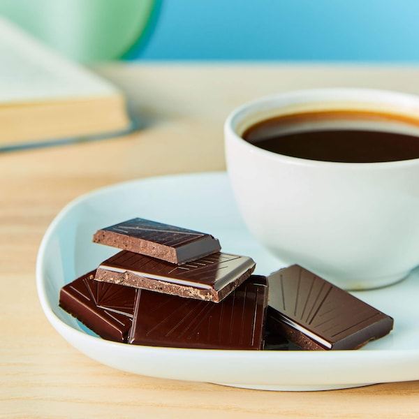 A plate of chocolate pieces and a cup of coffee on a wooden surface.
