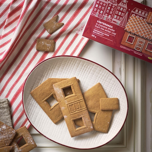 A plate of VINTERSAGA gingerbread on a plate with the red packaging behind it and a red and white striped fabric.