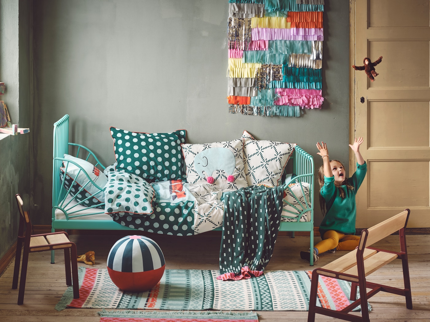 A playful Scandi-boho children's room with a green bed on the back wall and a lot of textiles on top. Small rugs and soft toys are lying on the floor.