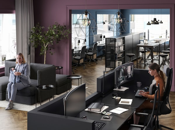 A plum-coloured reception area with a woman sat on black VALLENTUNA seating and another woman behind the black welcome desk.