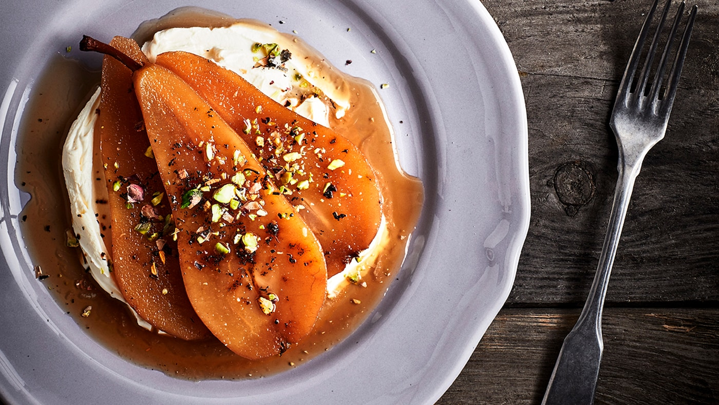 A portion of pears poached in Earl Grey tea served on a white plate on a rustic wooden table, with a fork on one side.