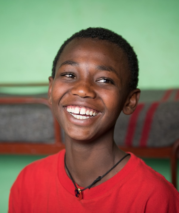 A portrait of a boy in a red T-shirt, smiling.