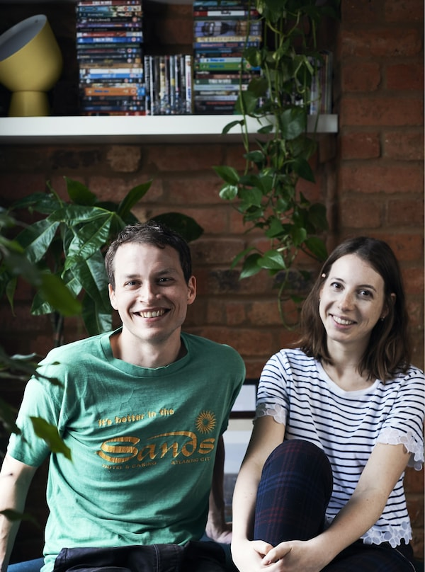 A portrait of a man and a woman in front of some green plants and a shelf.