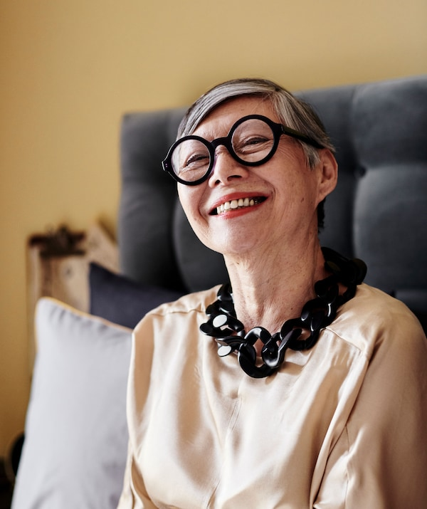 A portrait of a woman wearing black glasses and a black necklace.