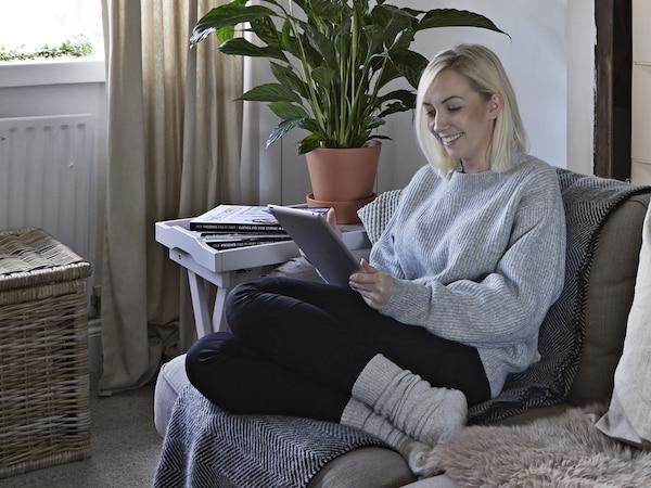 A portrait of Amanda, sitting on a sofa.