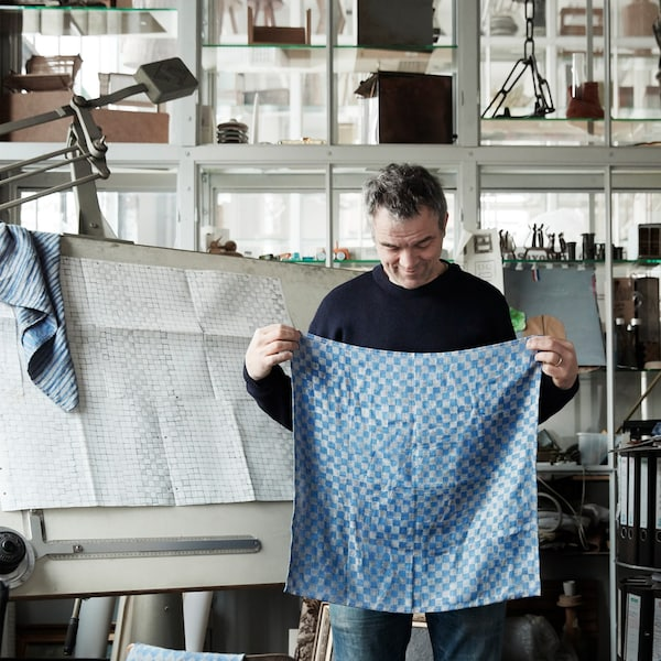 A portrait of Dutch designer Piet Hein Eik, pictured with a blue fabric sample from the IKEA INDUSTRIELL collection.