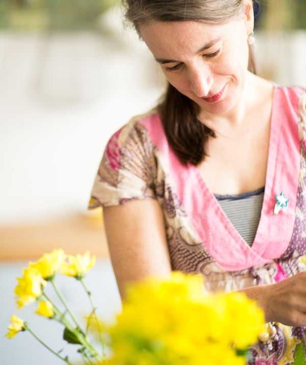 A portrait of Edna arranging yellow flowers.