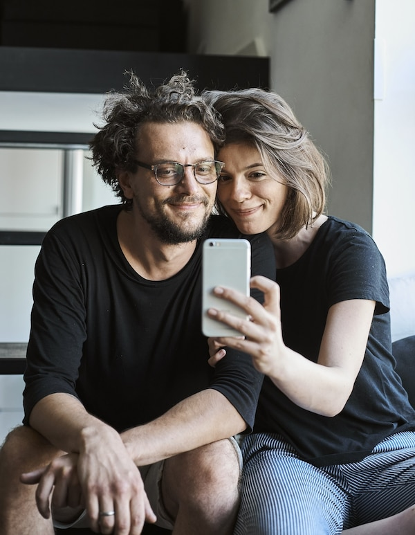 A portrait of Jurij and Konstancja taking a selfie on their stairs.