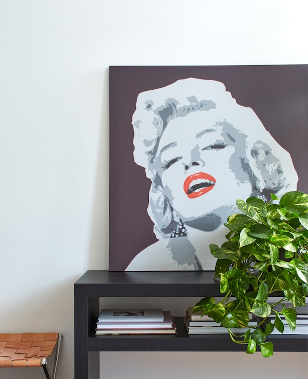 A portrait of Marilyn Monroe on a black coffee table against a white wall.