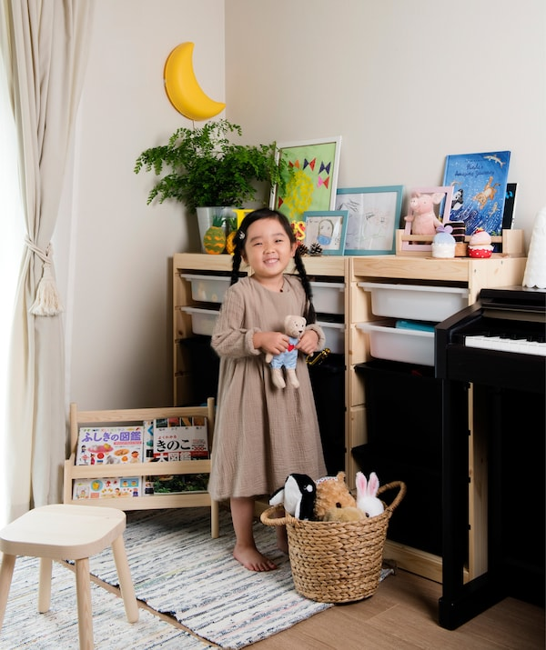 A portrait of Mieko's daughter standing next to her toy storage unit in the living room.