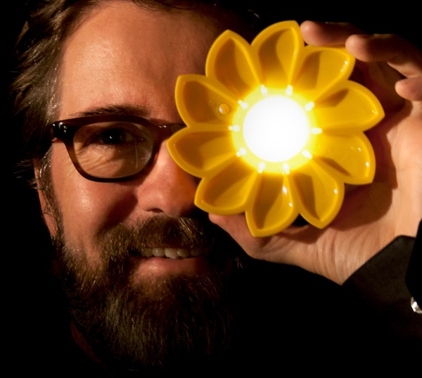 A portrait of social artist Olafur Eliasson holding up a yellow flower light as part of an energy initiative with IKEA.