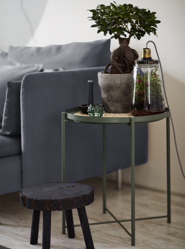 A pot plant on a tray table next to a grey sofa.