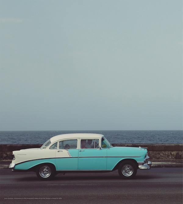 A print of a vintage car on a road.