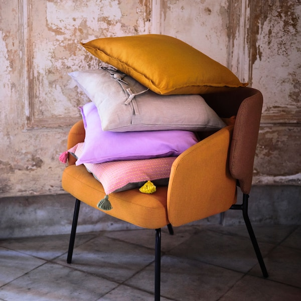 A pumpkin colored chair stacked with various throw pillows in purple, pink, and gray, set against a rustic beige wall.