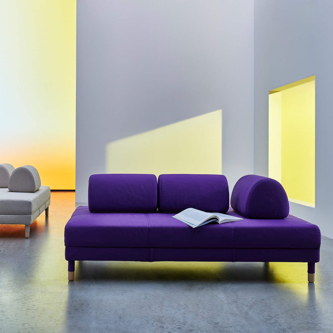 A purple FLOTTEBO sofa-bed with minimalist design, clean lines and rounded, movable cushions to place as you wish.