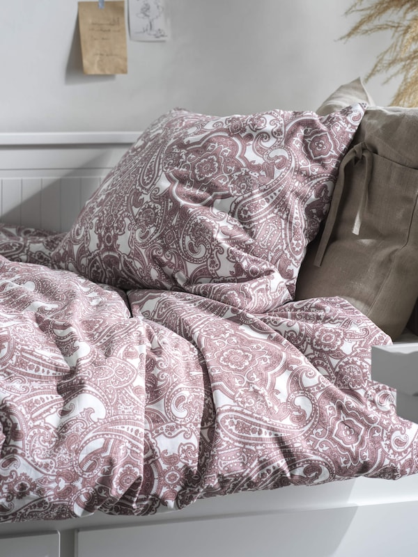 A purple patterned white duvet on a bed, linkin to the bedding page.