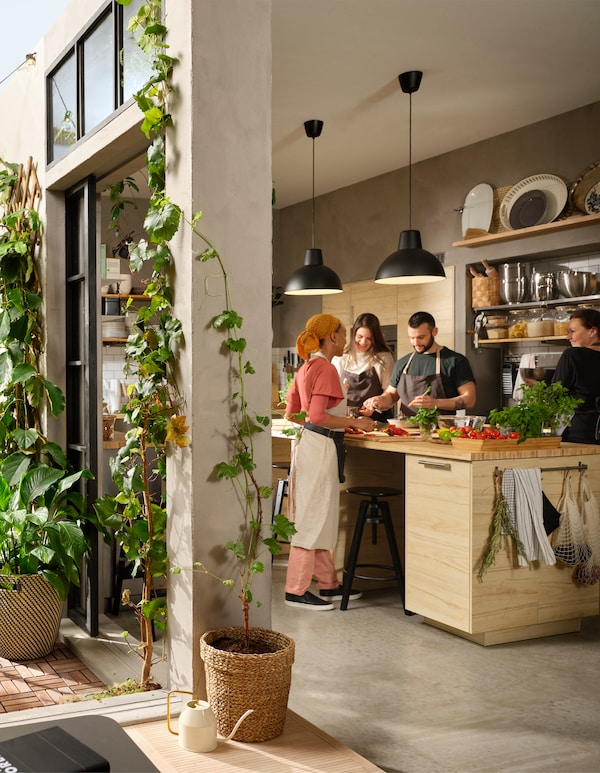 A quartet of people milling about a large kitchen island, preparing food. Doors stand ajar onto a yard with plants.